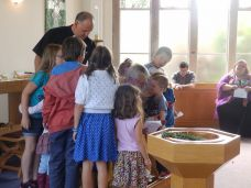 children and ministers gathered informally round a bishop, next to a font