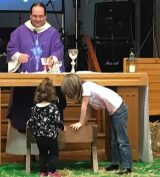 children playing round the altar while holy communion is being celebrated