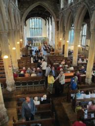 Church interior showing a variety of people coming to a service